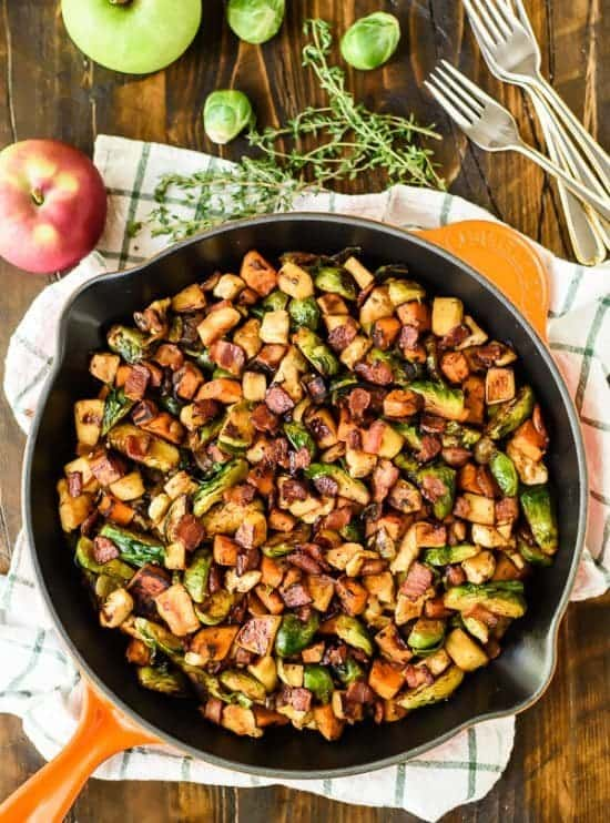 cast iron skillet with a dinner of Chicken, Bacon, Brussels Sprouts Skillet with Sweet Potatoes and Sauteed Apples
