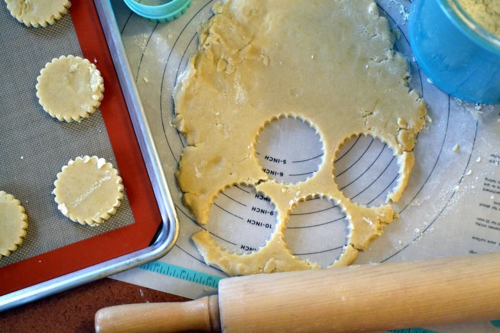 Lemon shortbread cookies being cut out of cookie dough and placed on a baking sheet