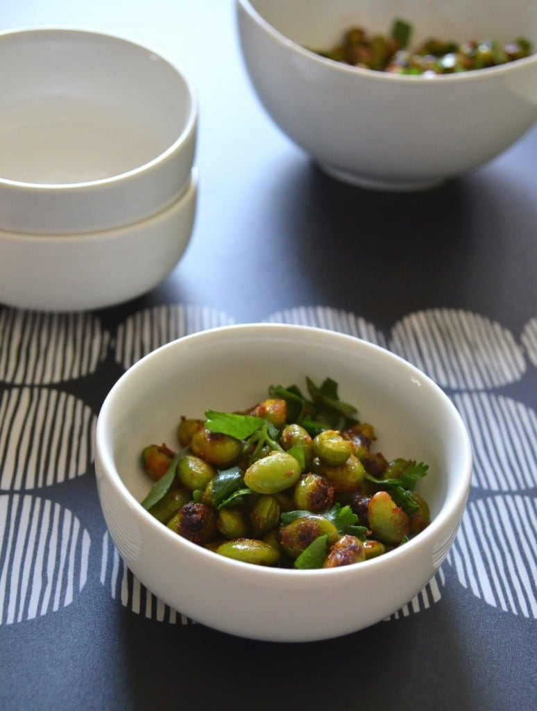 Two empty white bowls next to two bowls full of crispy edamame