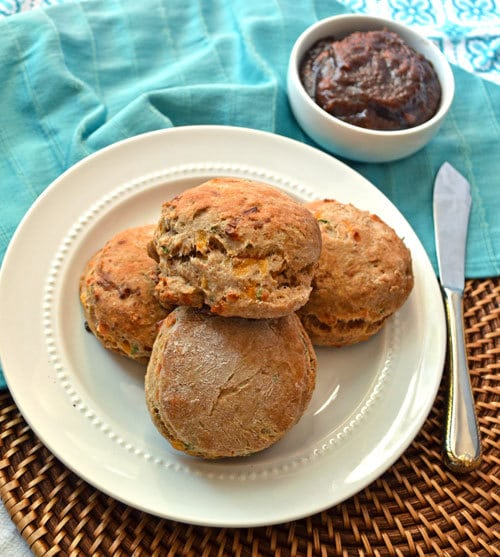 Apple butter and cheddar dill biscuits served on a plate with apple butter on the side