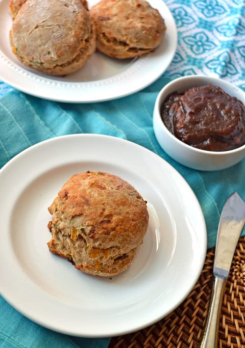 Cheddar dill biscuits served on white plates with apple butter on the side