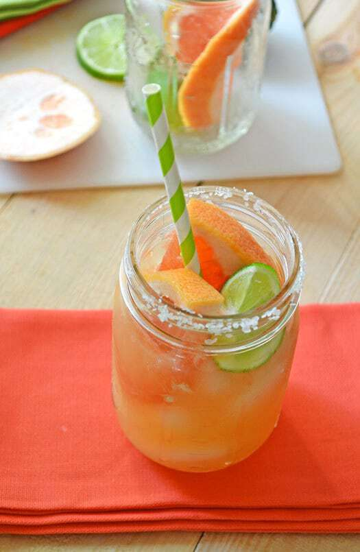 A chipotle grapefruit margarita served in a jar with sliced fruit