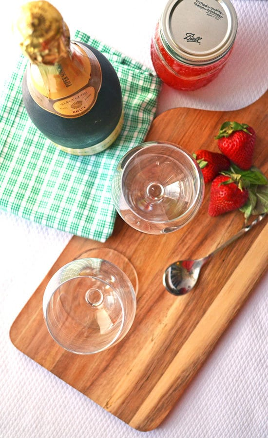 A bottle of champagne and strawberries next to two wine glasses