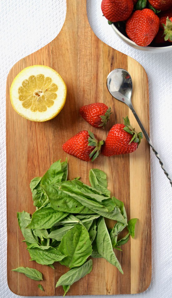 A wooden board with lemon, strawberries, and basil on top