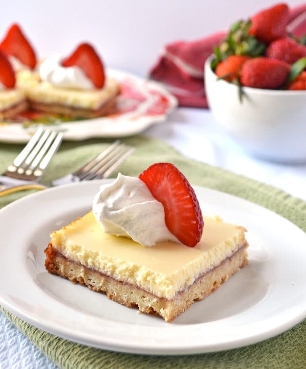 Strawberry Lemonade Shortbread Bars. Shortbread spread with strawberry jam and topped with lemon Greek yogurt cheesecake.