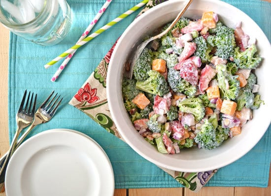 A bowl of strawberry broccoli salad on a blue placemat