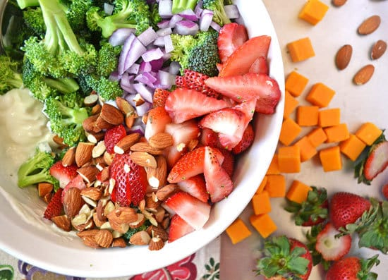 Strawberry broccoli salad ingredients in a bowl with almonds and cheese