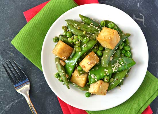 Healthy ginger tofu stir fry and peas on a white plate