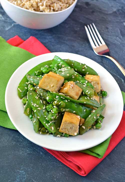 A plate of ginger tofu stir fry with sesame seeds and peas
