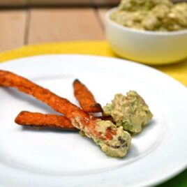 Three sweet potato fries dipped into avocado feta dip
