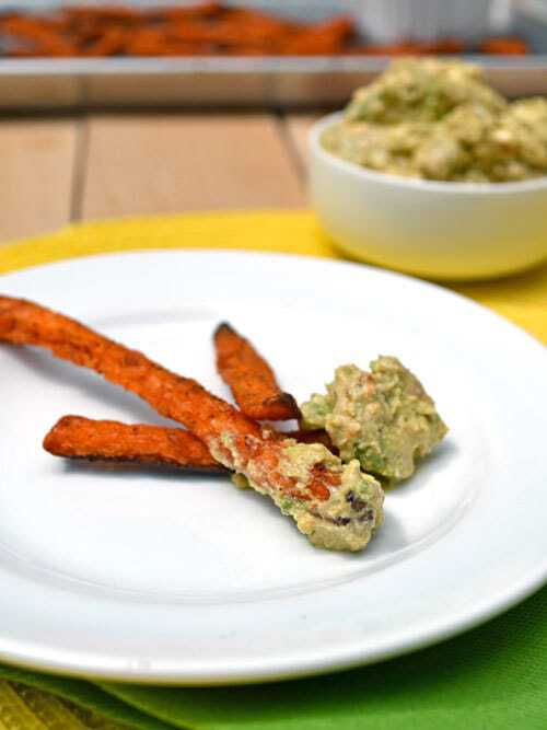 Three sweet potato fries on a white plate with avocado dip