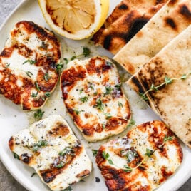 a plate with grilled halloumi cheese with herbs and lemon