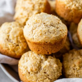 Two raspberry jam corn muffins in muffin wrappers