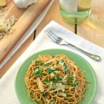 Garlic pasta on a green plate with Parmesan