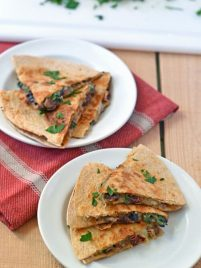 Two white plates with mushroom quesadillas