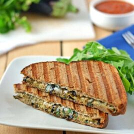 An eggplant ricotta grilled cheese on a white plate with arugula