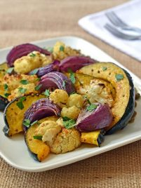 A white plate of oven roasted vegetables with lentils