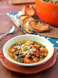 Minestrone soup in a white bowl with bread on the side