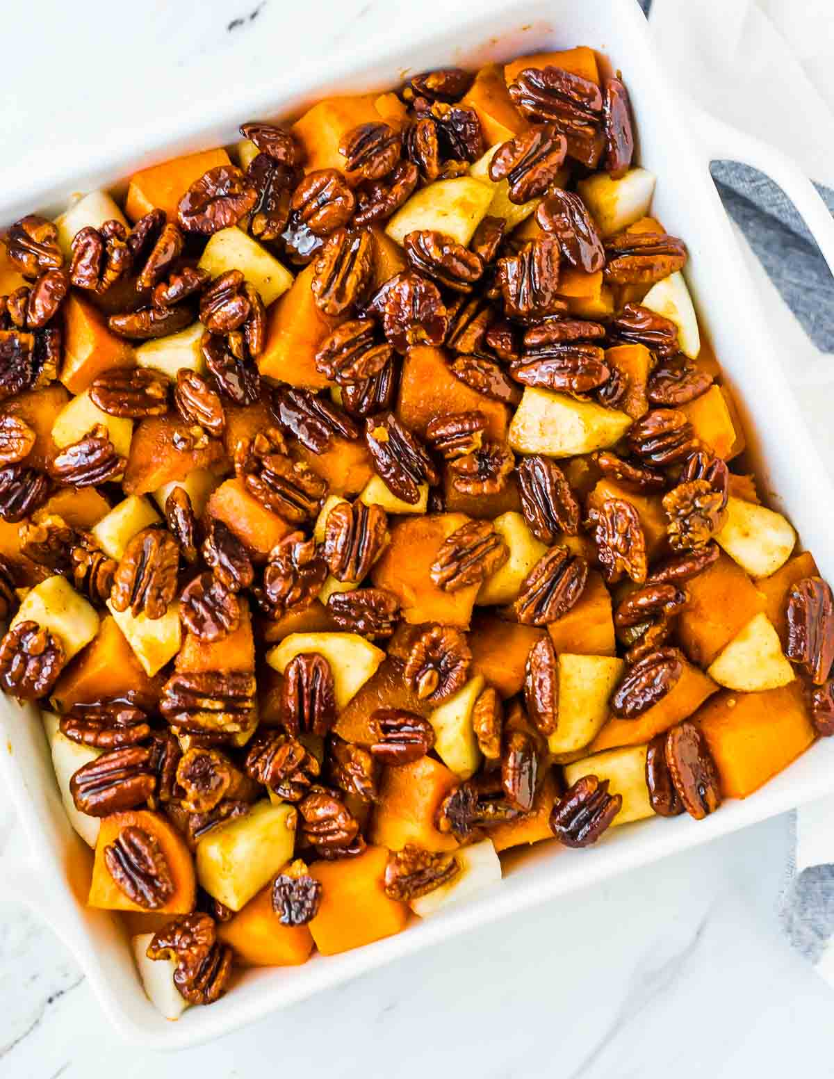 Glazed Sweet Potatoes with Whiskey Pecans. Roasted sweet potatoes and apples in a cinnamon honey butter sauce. Our favorite Thanksgiving side dish recipe! Great recipe for holidays, Christmas or dinner parties. Recipe at wellplated.com | @wellplated