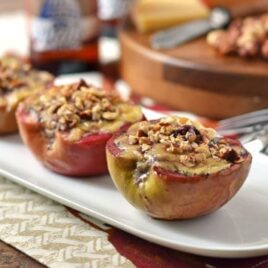Three baked apples with cheese and hazelnuts on a white serving platter