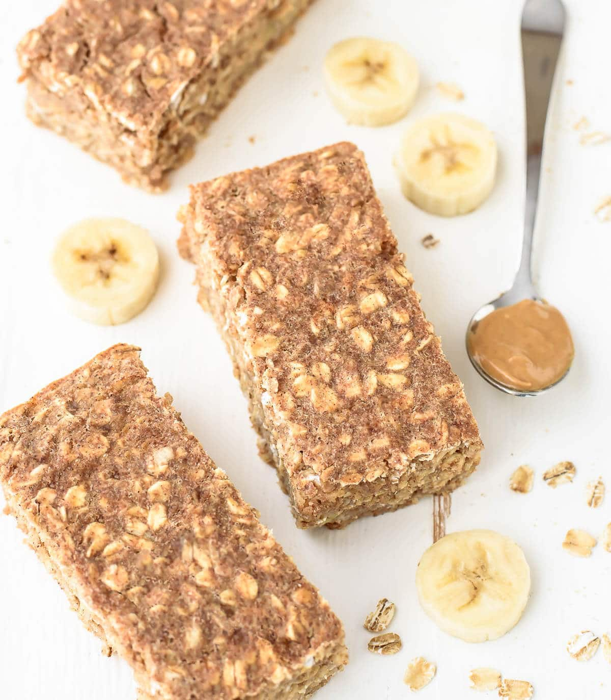 3 healthy Peanut Butter Banana Oatmeal Breakfast Bars surrounded by some of the ingredients needed to make them