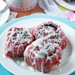 Three red velvet cinnamon rolls on a white plate with icing