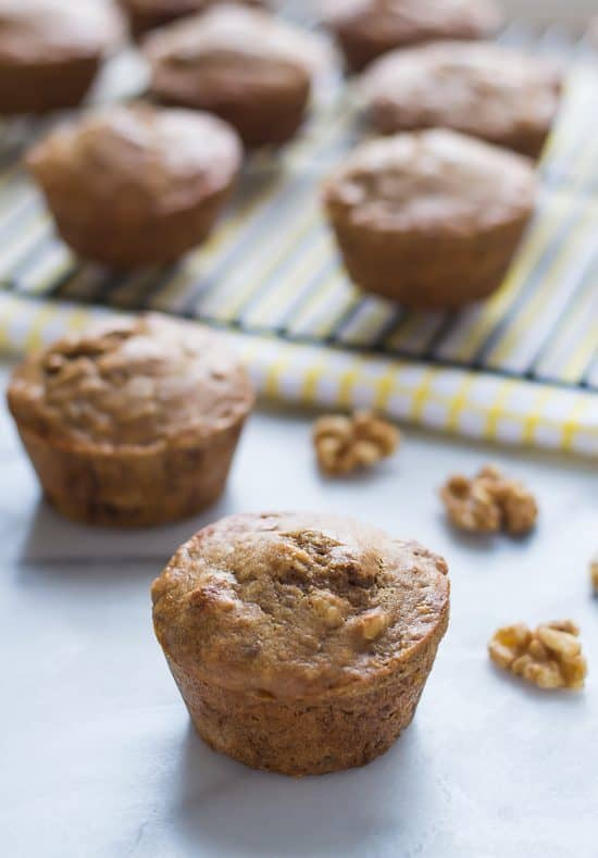 Healthy Banana Muffins with Walnuts on a blue and yellow striped kitchen towel