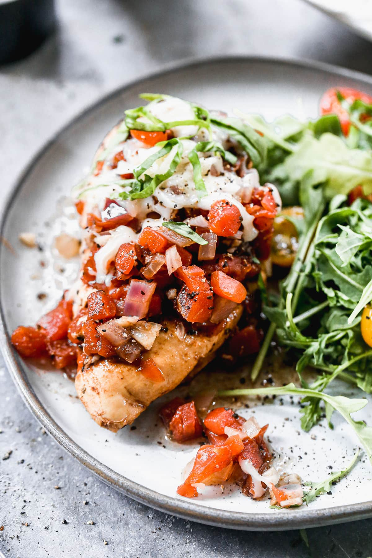 a piece of healthy crockpot italian chicken on a plate with tomatoes, mozzarella, and arugula