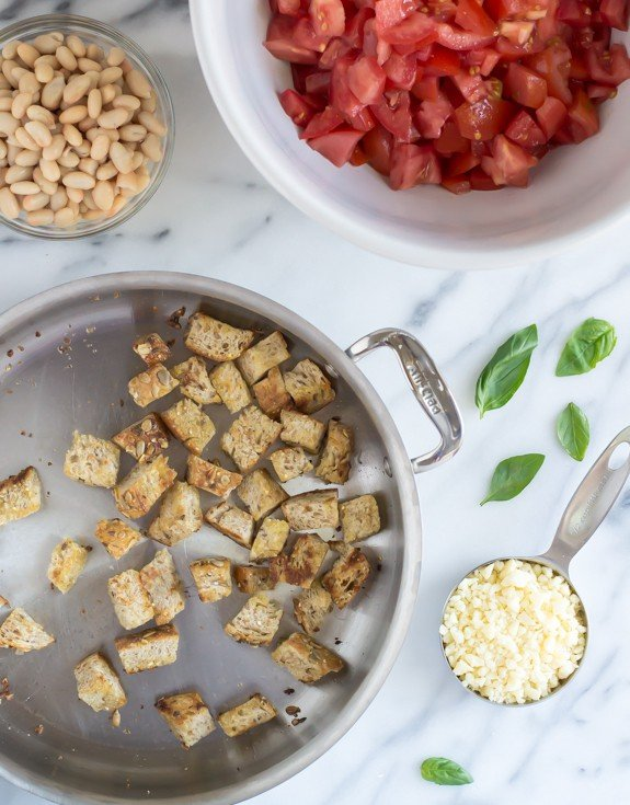 Homemade croutons toasting in a stainless skillet with bowls of white beans, fresh tomatoes, basil, and shredded parmesan next to it