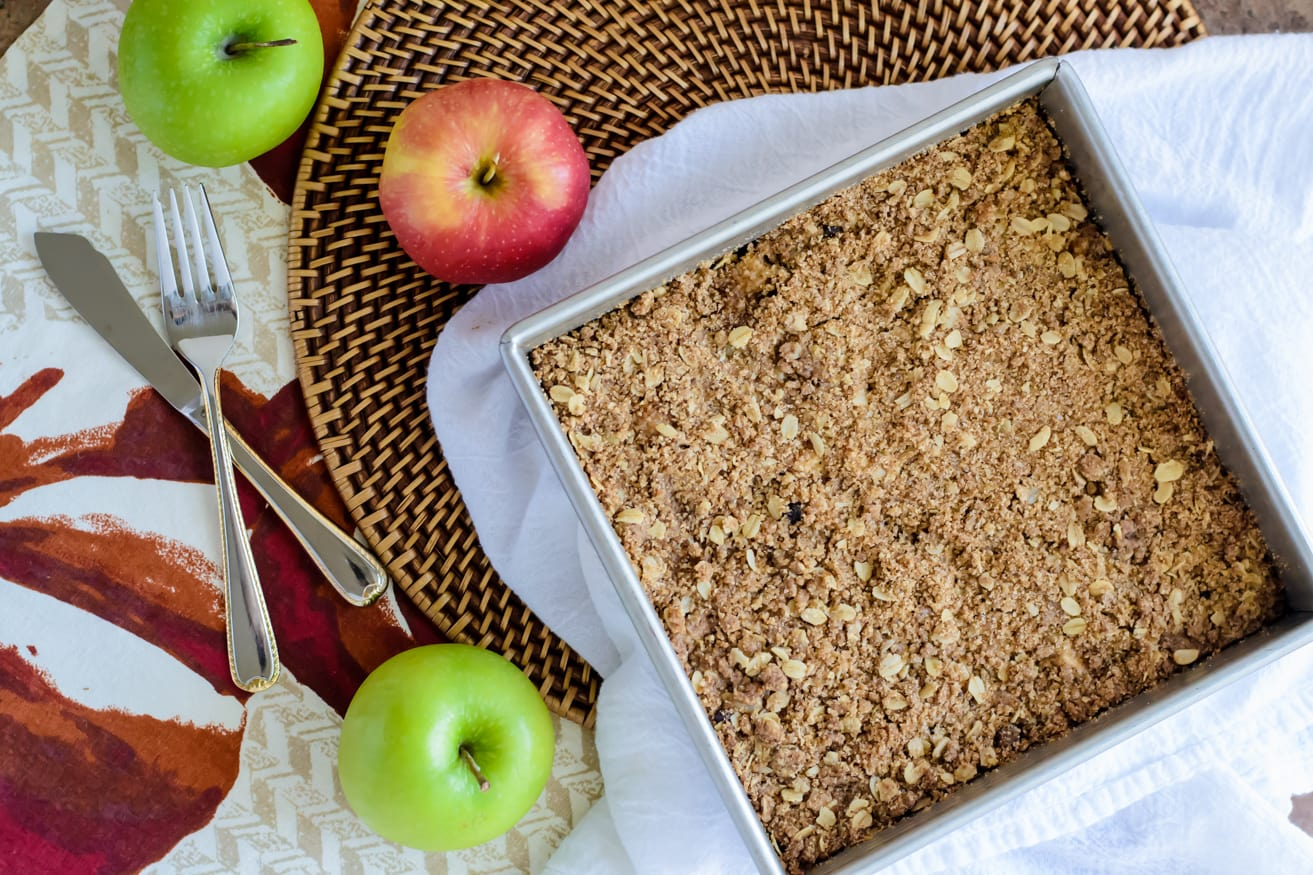 A square pan of freshly baked gooey caramel apple bars on a table with green and red apples and a white tea towel