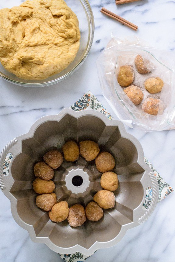 Homemade Pumpkin Monkey Bread - Rolling dough in sugar