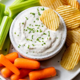 A white bowl of ranch dip with carrots and celery on the side