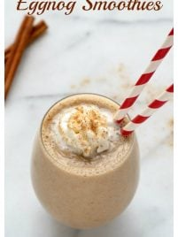 An eggnog smoothie in a glass with red and white straws