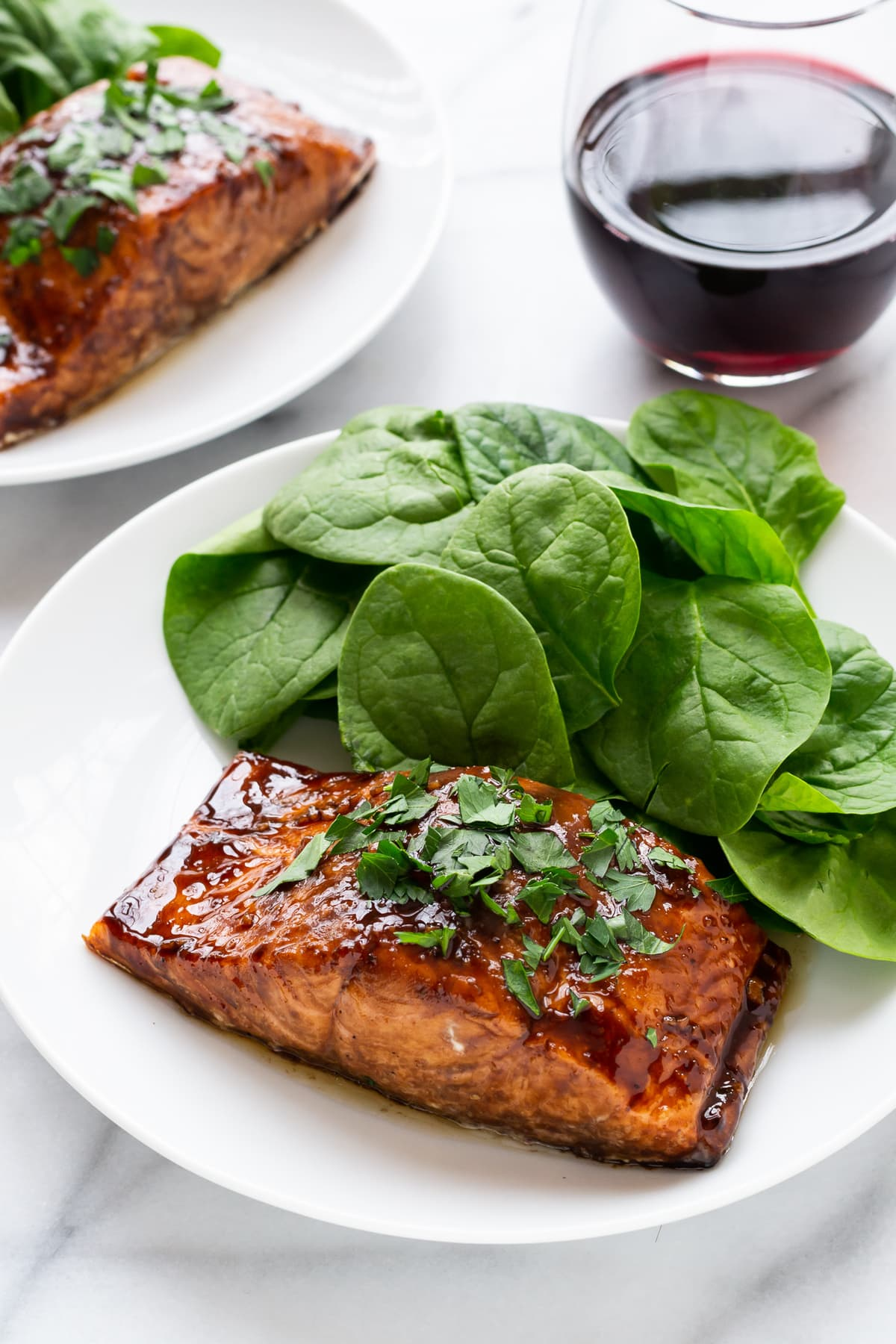 salmon filet coated with a balsamic glaze on a white dinner plate with fresh spinach