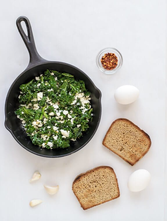 Love this fast and healthy dinner! Sauteed kale with feta and runny eggs on toast. Like eggs Florentine, but easier and good for you!