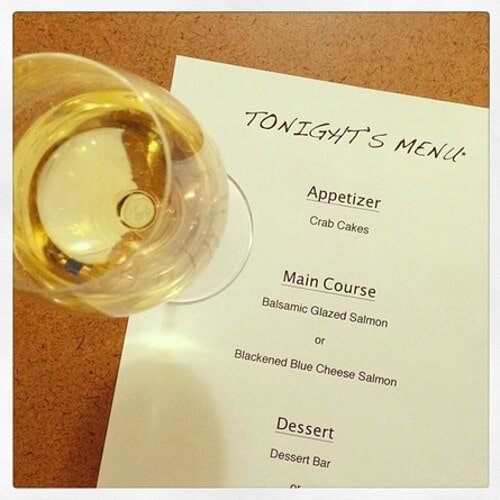 homemade romantic dinner menu next to a glass of white wine