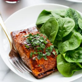 white dinner plate with Balsamic Glazed Salmon and fresh spinach