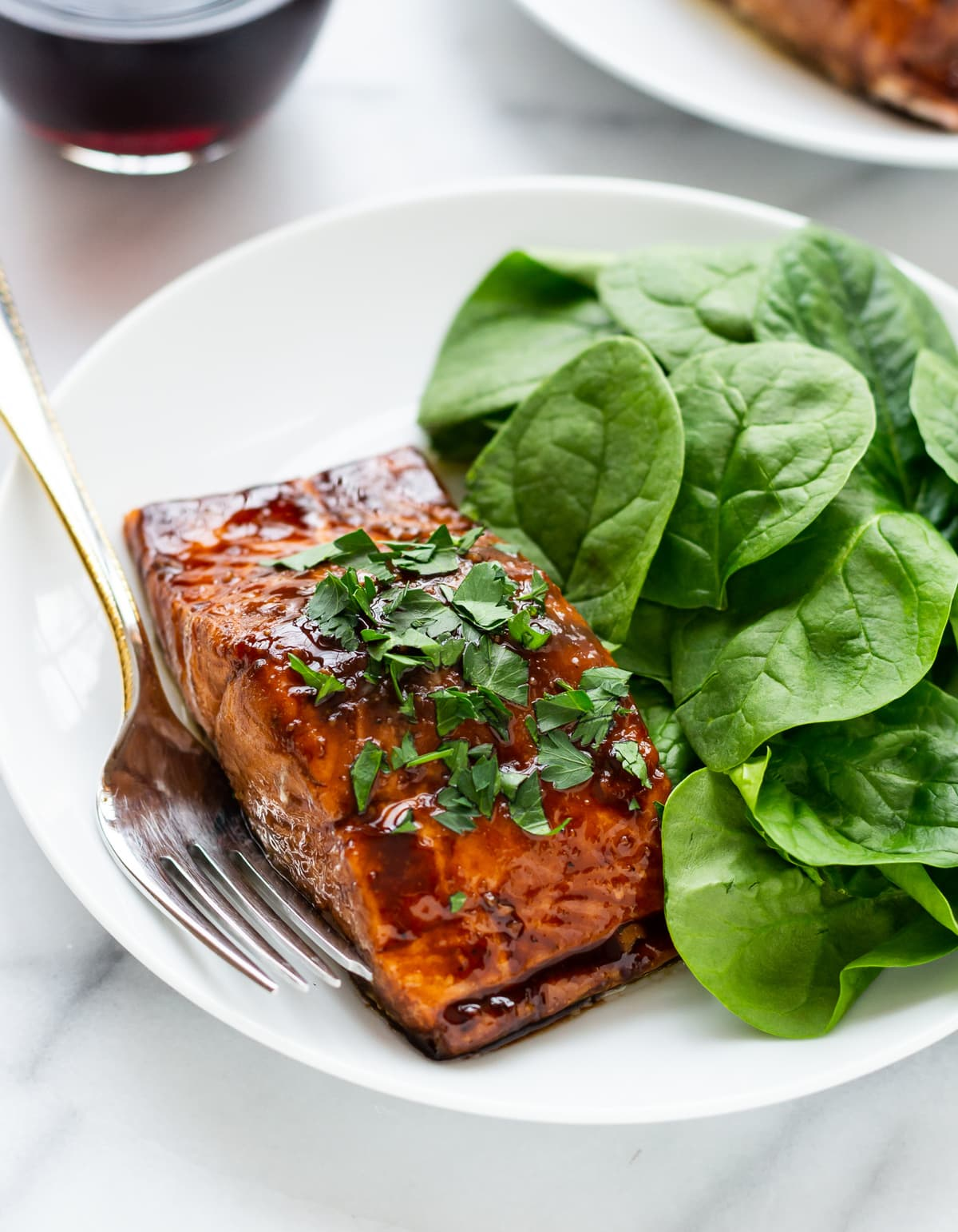 balsamic glazed salmon on a white dinner plate, next to fresh spinach leaves