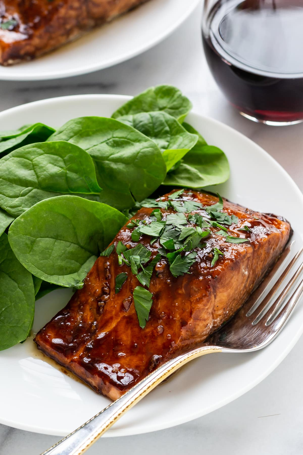dinner serving of Balsamic Glazed Salmon, spinach, and a glass of red wine