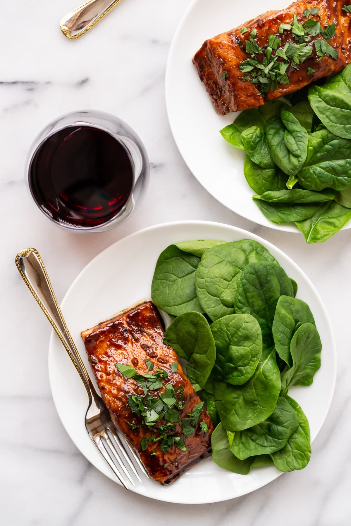 two white dinner plates with balsamic glazed salmon and glasses of red wine