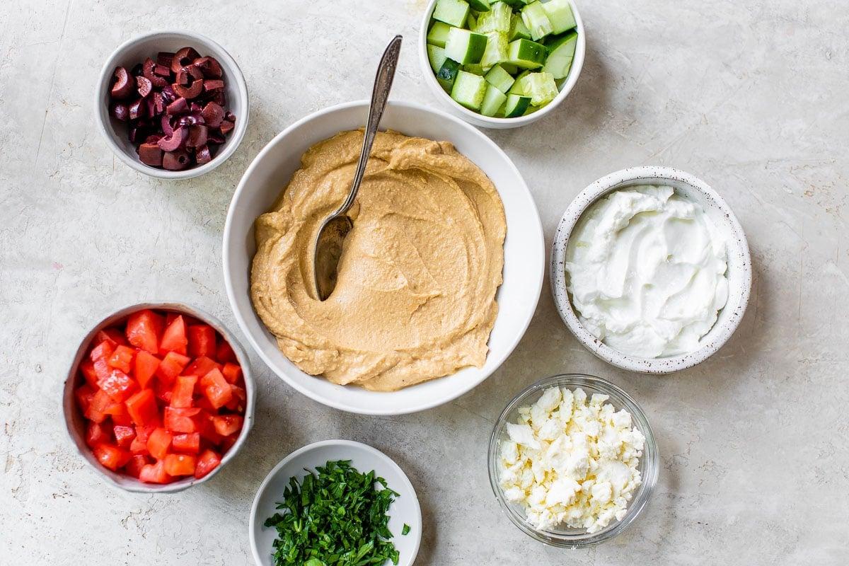 Greek Layer Dip ingredients in bowls: feta, hummus, tomatoes, parsley, olives