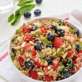 Red white and blue quinoa fruit salad in a white bowl