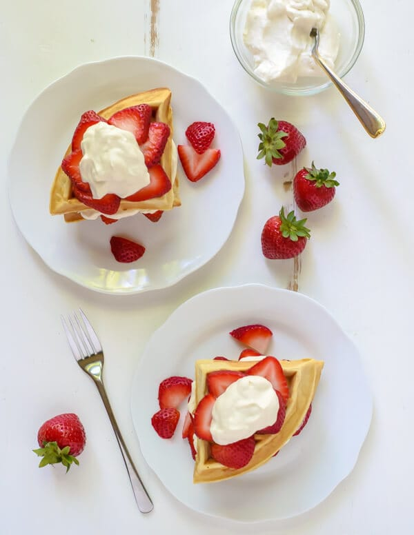 Overhead photo showing two white plates of Strawberry Shortcake Waffles with Maple Whipped Cream