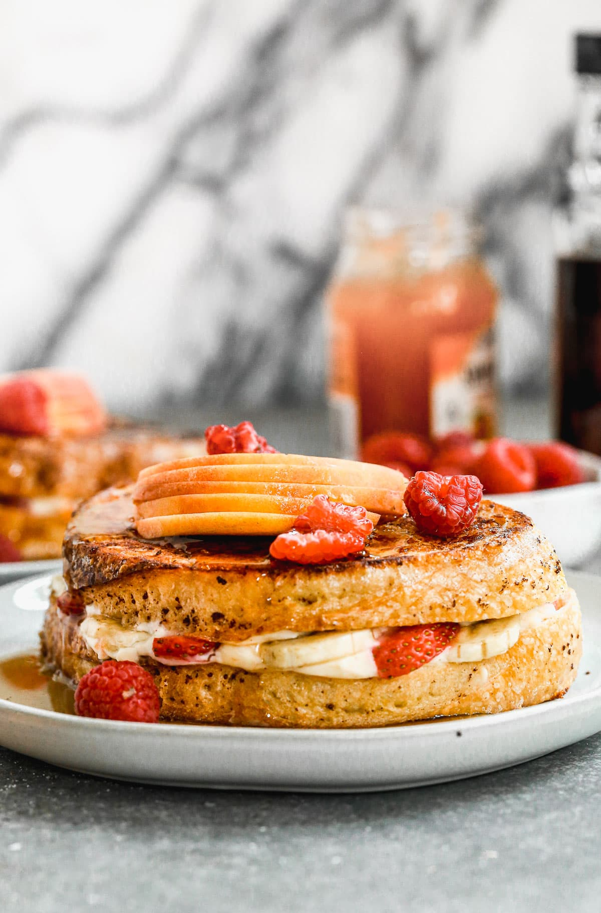 A stuffed french toast sandwich with banana, strawberry, and maple syrup