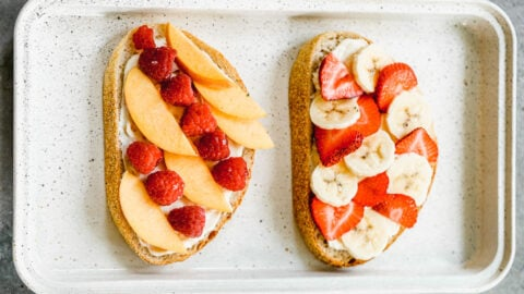 two slices of bread spread with cream cheese filling and fresh fruit for making stuffed french toast