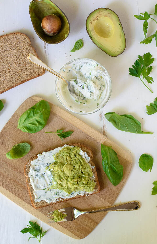Spreading goat cheese and avocago on wheat bread with herbs