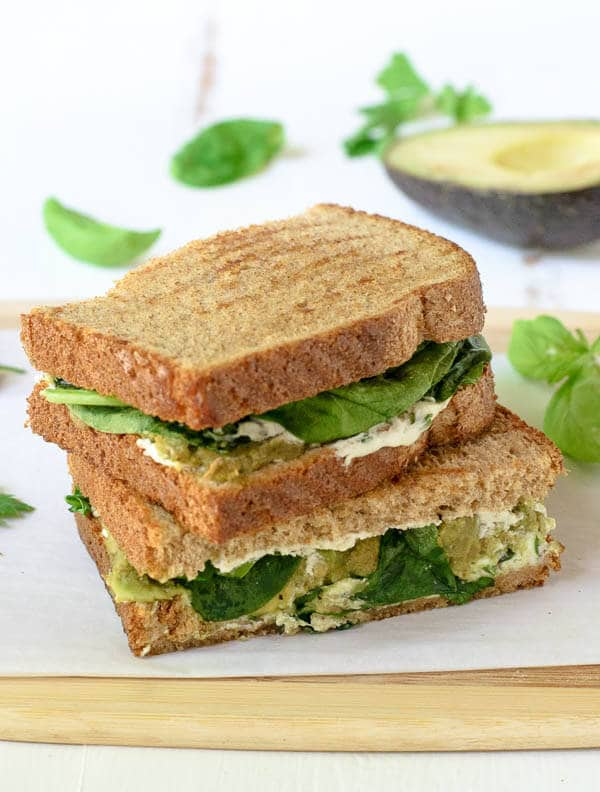 Avocado Grilled Cheese halves stacked on parchment paper.