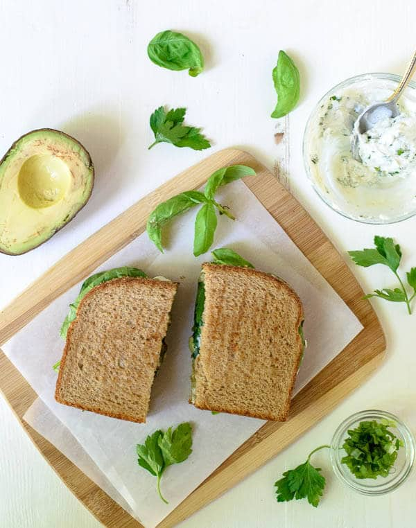 Avocado Grilled Cheese with Herbed Goat Cheese and Garlic on a piece of parchment paper and wood cutting board