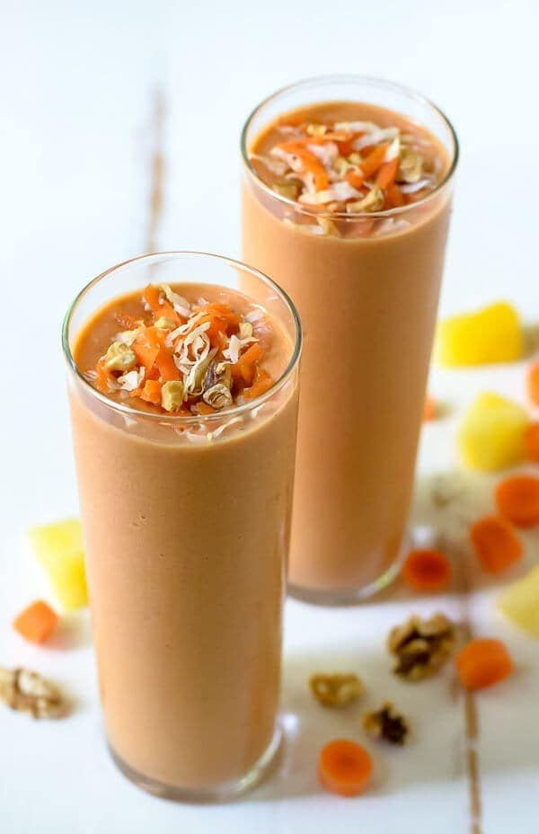 Healthy carrot smoothies in tall glasses topped with shredded carrot, coconut and walnuts