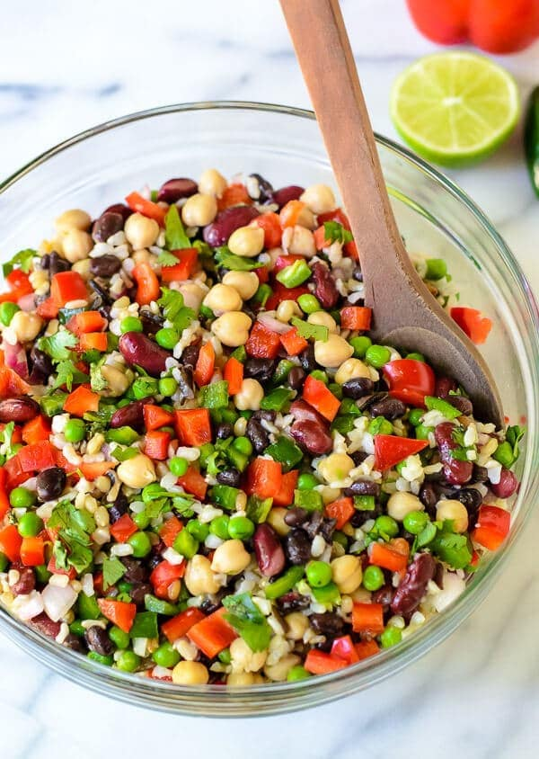 Mexican Three Bean Salad with Wild Rice in a glass bowl with a wooden spoon